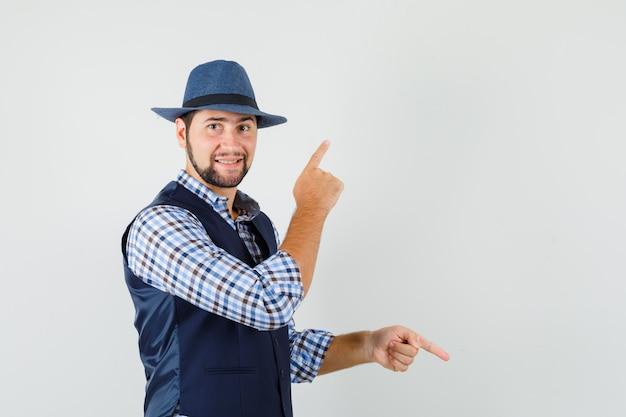 Młody człowiek, wskazując palcami w górę iw dół w koszuli, kamizelce, kapeluszu i patrząc wesoło, widok z przodu.
