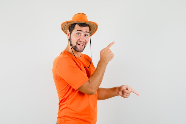 Młody człowiek wskazując palcami w górę iw dół w pomarańczowej koszulce, kapeluszu i radosnym wyglądzie, widok z przodu.