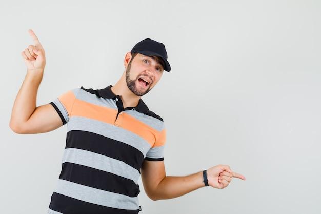 Młody człowiek, wskazując palcami w górę iw dół w t-shirt, czapkę i szczęśliwy, widok z przodu.