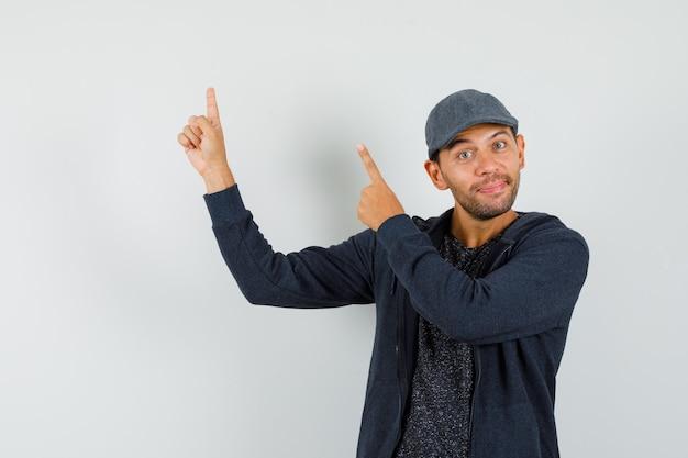 Młody człowiek wskazując palcami w t-shirt, kurtkę, czapkę i wyglądający wesoło.