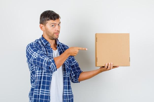 Młody człowiek wskazując palcem na karton w widoku z przodu koszuli.