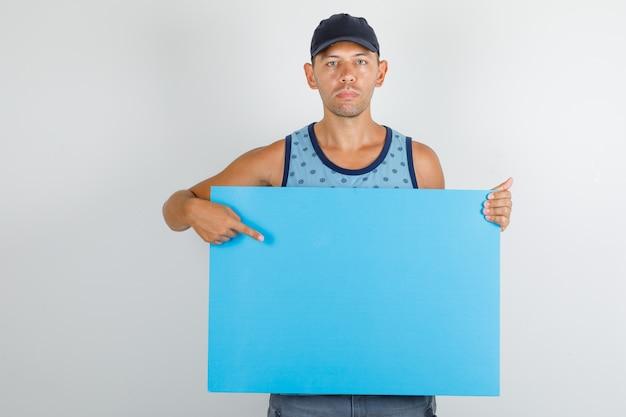 Młody człowiek wskazując palcem na plakat w niebieskim podkoszulku z czapką