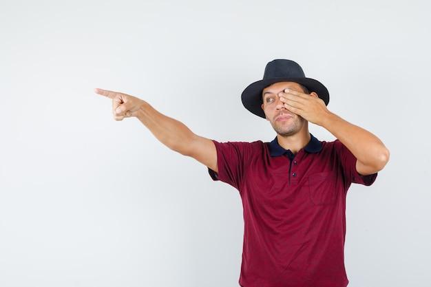 Młody człowiek wskazując ręką na oko w t-shirt, widok z przodu kapelusz.
