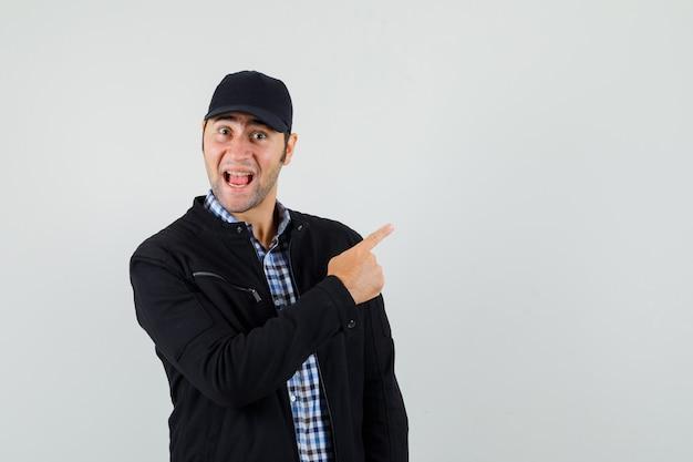 Młody człowiek, wskazując w prawym górnym rogu w koszuli, kurtce, czapce i patrząc szczęśliwy, widok z przodu.