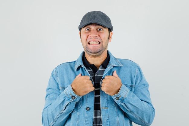 Młody człowiek wskazujący na siebie z zaciśniętymi zębami w koszulce, marynarce, czapce i wyglądający na zaskoczonego