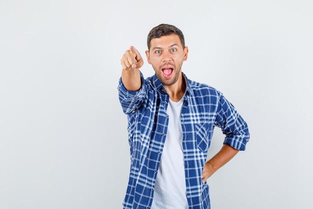Młody człowiek wskazujący palec ręką w talii w koszuli, widok z przodu.