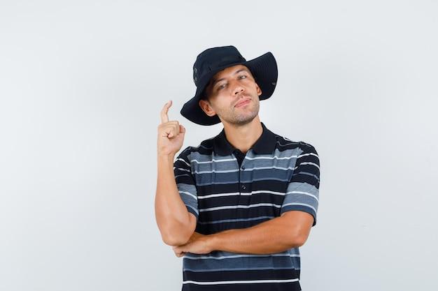 Młody człowiek wskazuje w t-shirt, kapelusz i wygląda pewnie. widok z tyłu.