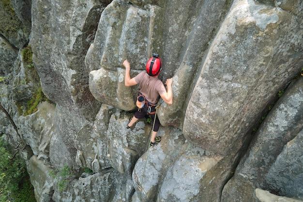 Młody człowiek wspinaczka stroma ściana skalistej góry. wspinacz pokonuje trudną trasę. angażowanie się w koncepcję sportów ekstremalnych.