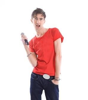 Młody człowiek współczesny z mikrofonem na białym tle na białej ścianie. zdjęcie z miejsca na kopię