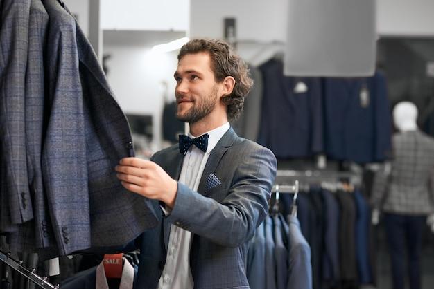 Młody człowiek wybiera garnitury w butiku.