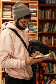 Młody człowiek wybiera książkę w sklepie.
