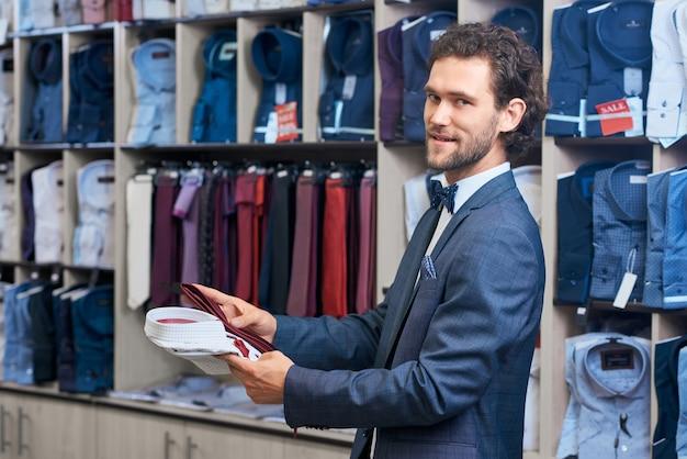 Młody człowiek wybiera nową koszulę kolekcji w sklepie.