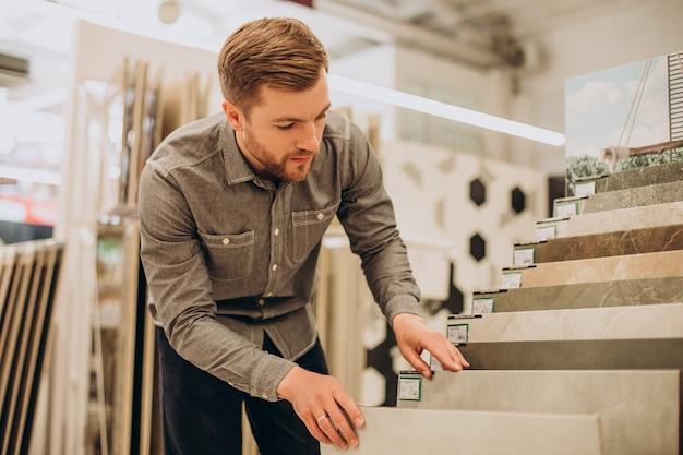 Młody człowiek wybiera płytki na rynku budowlanym