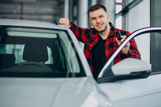 Młody człowiek wybiera samochód w samochodowej sala wystawowej