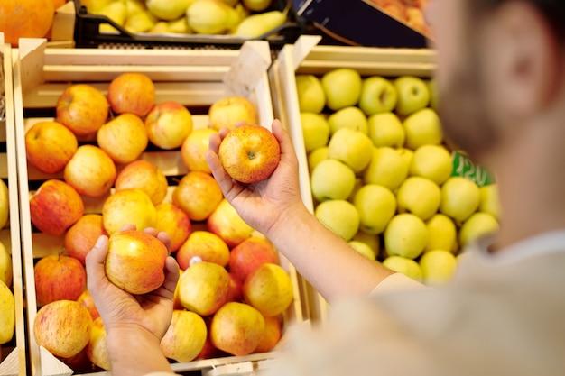 Młody człowiek wybiera świeże dojrzałe żółte jabłka stojąc przy wyświetlaczu owoców w supermarkecie