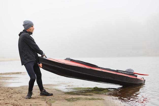 Młody człowiek wyciąga łódź na brzeg, trzymając w rękach kajak i patrząc na piękną rzekę, ubrany w sportowe ubrania
