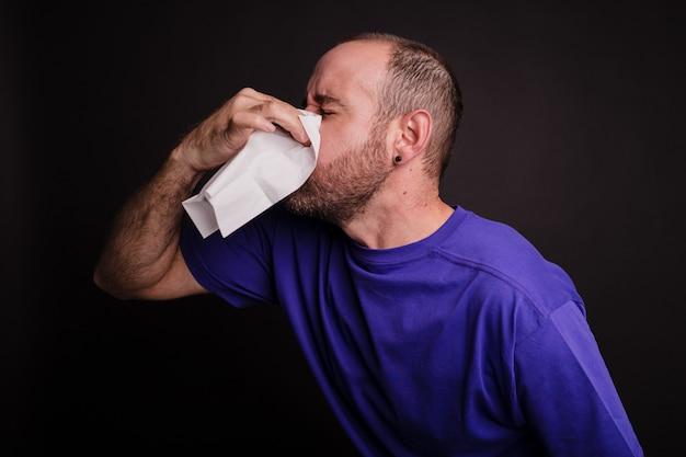 Młody człowiek wycierając nos papierowym ręcznikiem