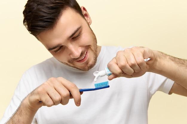 Młody człowiek wyciska pastę do zębów na szczoteczce