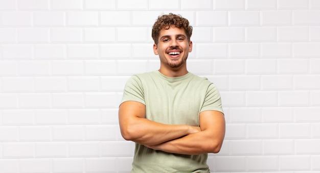 Młody człowiek wyglądający jak szczęśliwy, dumny i zadowolony człowiek, który osiągnął sukces, uśmiechając się z założonymi rękami