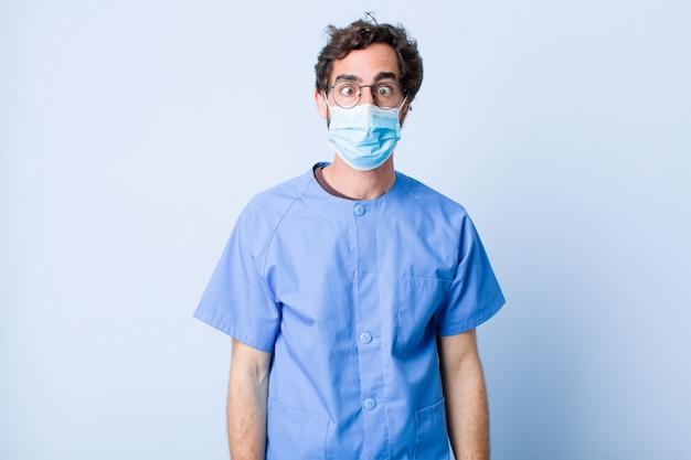 Młody człowiek wyglądający na głupkowatego i zabawnego z głupim zezem, żartujący i wygłupiający się. koncepcja koronawirusa