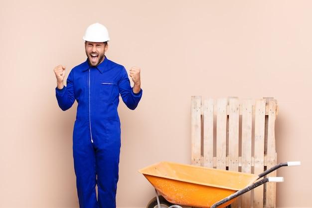 Młody człowiek wyglądający na niezwykle szczęśliwego i zaskoczonego, świętujący sukces, krzyczący i skaczący koncepcja budowy