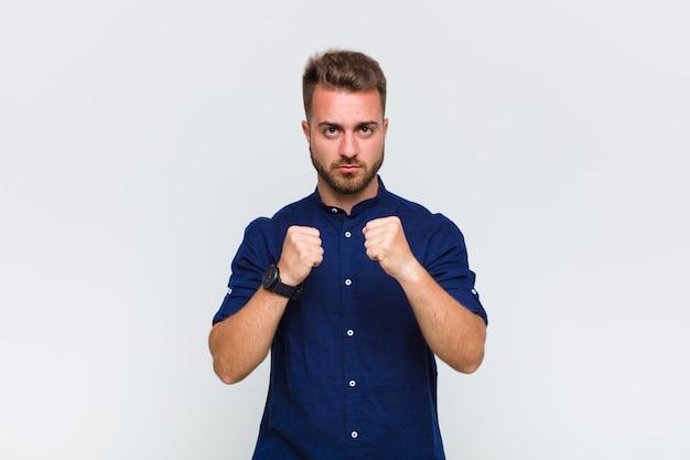 Młody człowiek wyglądający na pewnego siebie, wściekłego, silnego i agresywnego, z pięściami gotowymi do walki w pozycji bokserskiej