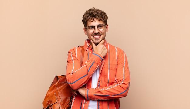 Młody człowiek wyglądający na szczęśliwego i uśmiechniętego z ręką na brodzie, zastanawiający się lub zadający pytanie, porównujący opcje. koncepcja studenta