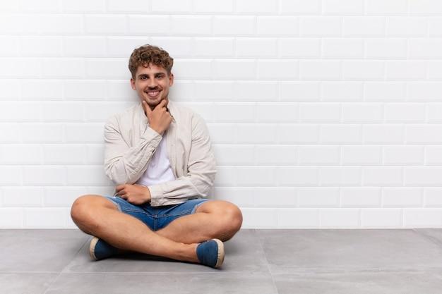 Młody człowiek wyglądający na szczęśliwego i uśmiechniętego z ręką na brodzie, zastanawiający się lub zadający pytanie, porównujący opcje