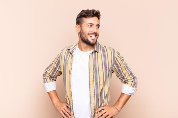 Młody człowiek wyglądający na szczęśliwego, wesołego i pewnego siebie, uśmiechającego się dumnie i patrzącego w bok z obiema rękami na biodrach