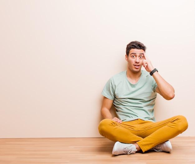 Młody człowiek wyglądający na zaskoczonego, z otwartymi ustami, zszokowany, uświadamiający sobie nową myśl, pomysł lub koncepcję siedzącą na podłodze