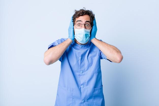Młody człowiek wyglądający nieprzyjemnie zszokowany, przestraszony lub zmartwiony, z szeroko otwartymi ustami i obejmujący dłońmi oba uszy. koncepcja koronawirusa