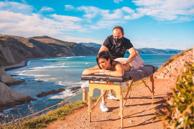 Młody człowiek wykonujący masaż na łonie natury na wybrzeżu blisko morza, spełnienie marzeń, masażystka z maską w czasie pandemii koronawirusa