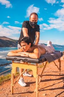 Młody człowiek wykonujący masaż na łonie natury na wybrzeżu w pobliżu morza, masażystka z maską na twarz podczas pandemii koronawirusa