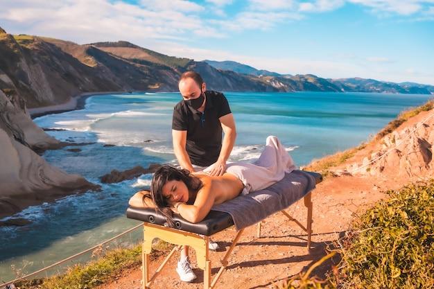Młody człowiek wykonujący masaż przyrodniczy na wybrzeżu w pobliżu morza, marzenie się spełniło