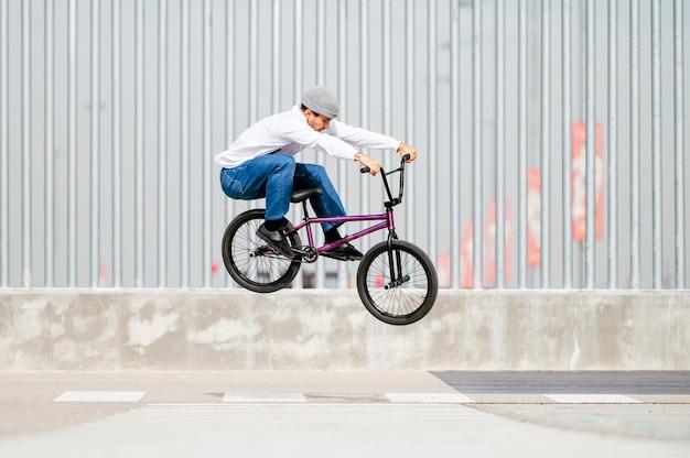 Młody człowiek wykonujący sztuczki na rowerze typu flatland bmx