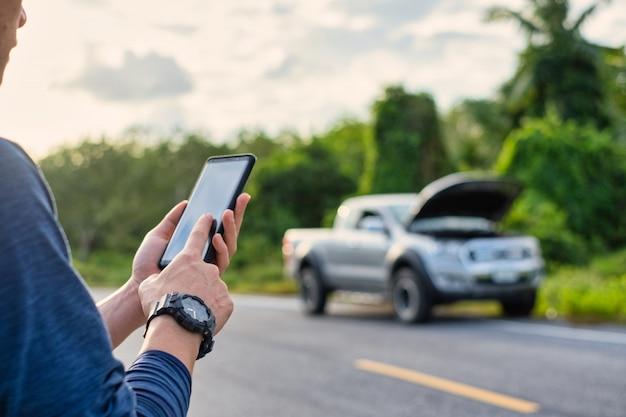 Młody człowiek wykonuje telefon podczas zepsutego samochodu. człowiek potrzebuje pomocy.