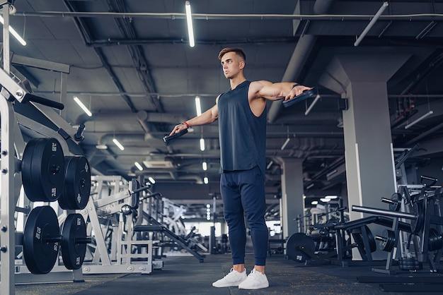 Młody człowiek wykonywania hantle boczne podnoszenie - ćwiczenia na ramiona