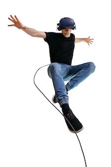Młody człowiek wyobraża sobie siebie superbohatera, używając okularów vr do grania w gry komputerowe