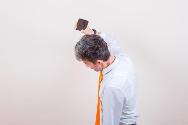 Młody człowiek wyrzuca telefon komórkowy w koszuli i wygląda na wściekłego