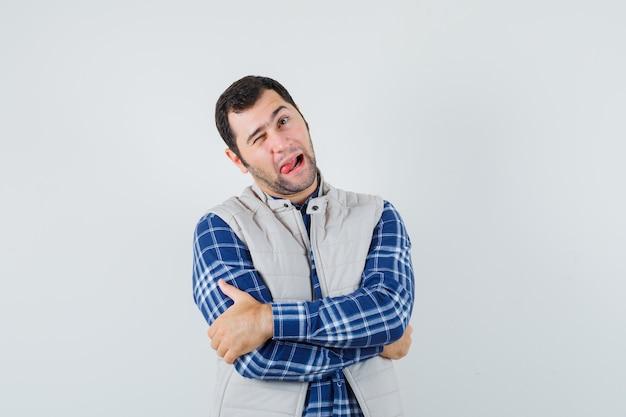 Młody człowiek wystaje język podczas mrugania w koszuli, kurtce bez rękawów i wygląda zabawnie, widok z przodu.
