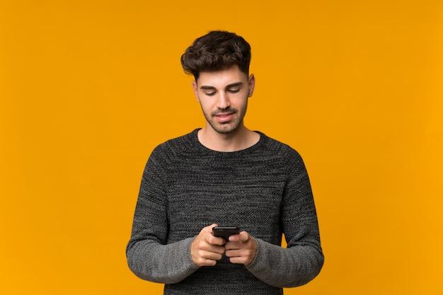 Młody człowiek, wysyłając wiadomość lub e-mail z telefonu komórkowego