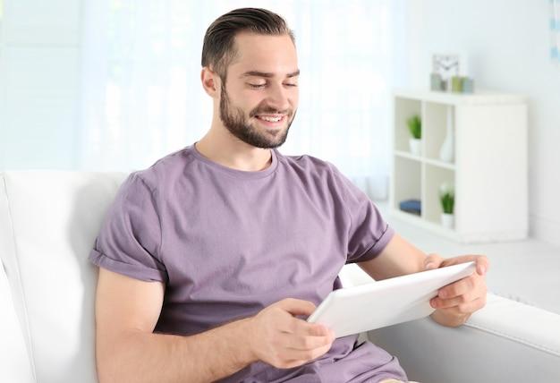Młody człowiek wyszukiwanie informacji za pomocą tabletu w domu