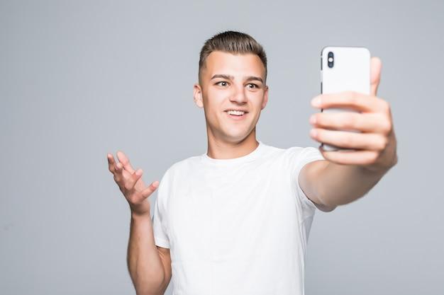 Młody człowiek wziąć selfie na szarym tle