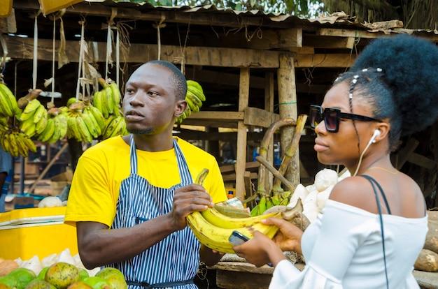 Młody człowiek z afrykańskiego targu czuje się podekscytowany, gdy sprzedaje swoje towary klientowi.