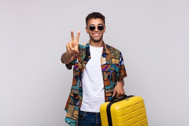 Młody człowiek z ameryki południowej uśmiechnięty i wyglądający przyjaźnie, pokazujący numer dwa lub sekundę z ręką do przodu, odliczający