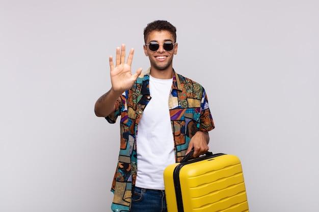 Młody człowiek z ameryki południowej uśmiechnięty i wyglądający przyjaźnie, pokazujący numer pięć lub piąty z ręką do przodu, odliczający