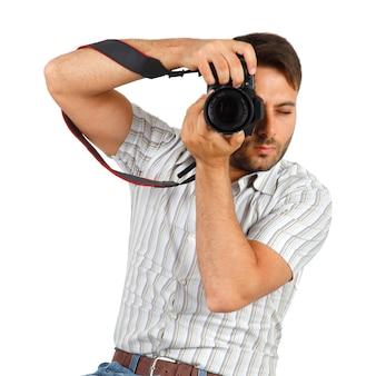 Młody człowiek z aparatem na białym tle na białej ścianie