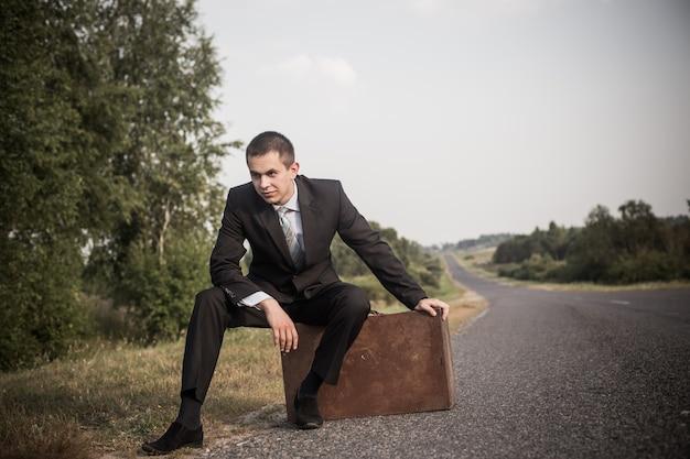Młody człowiek z bagażem na drodze