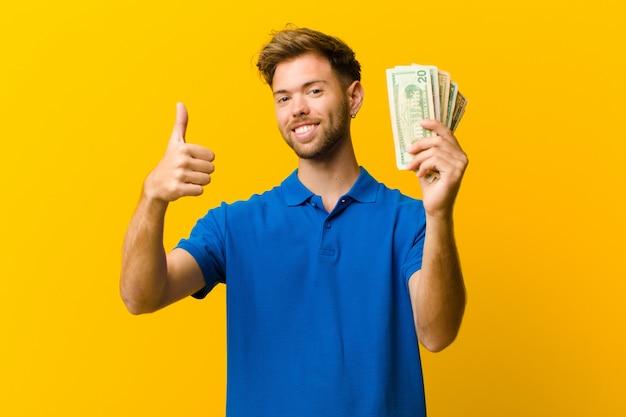 Młody człowiek z banknotami pomarańczowymi