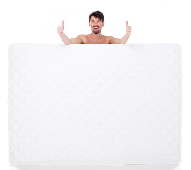 Młody człowiek z białym materacem